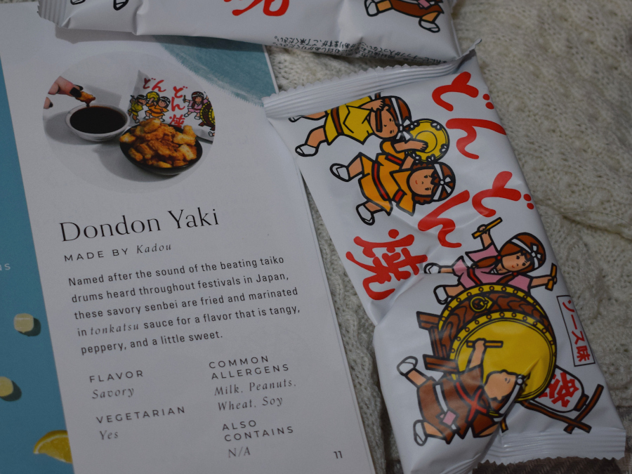 Two packets of baked teriyaki flavoured snacks next to a leaflet describing them