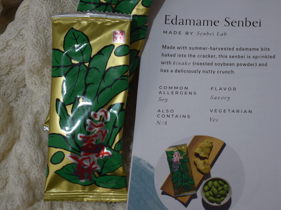 Two packed of baked edamame crackers next to a leaflet describing them