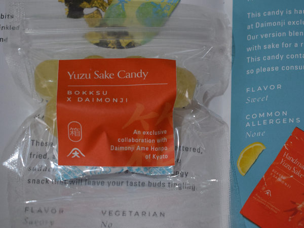 A packet of yuzu and sake hard candy next to a leaflet describing it